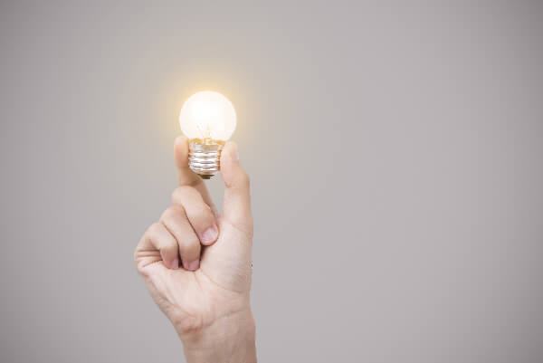 Illustration de la compétence ingénierie : un main tient une ampoule allumée