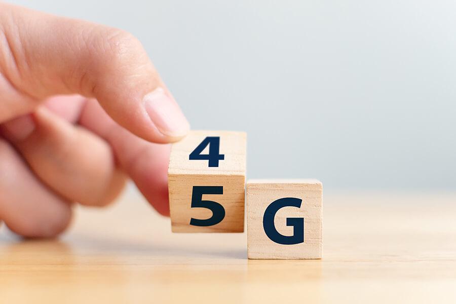 Passage de la 4G à la 5G : une main tourne un cube où il est écrit 4 sur une face et 5 sur l'autre. Un autre cube est posé à côté avec un G écrit dessus.